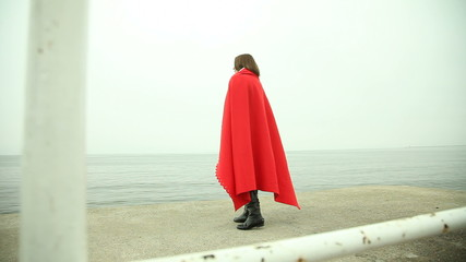 Lonely girl in red blanket on pier looking at the sea
