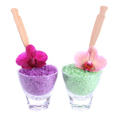 Color sea salt in glass bowls and  orchid flowers, isolated