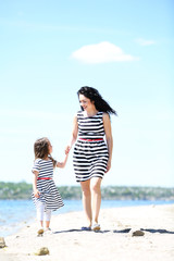 Happy mom and daughter. Walk on the beach