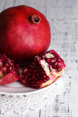 Ripe pomegranates on plate, on color wooden background
