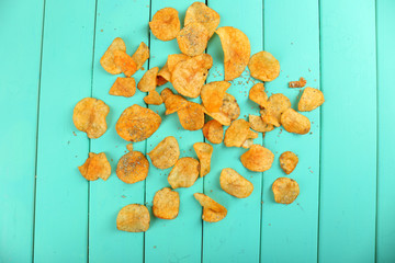 Homemade potato chips on color wooden table