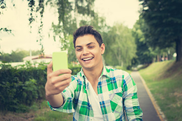 Hispanic young man taking a selfie outdoors in park