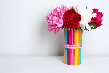 Beautiful flowers in colorful pencils vase in interior design