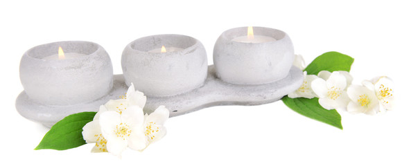 Candles with jasmine flowers isolated on white