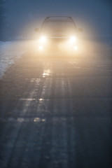 Headlights of car driving in fog