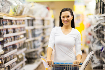 young woman pushing trolley in supermarket