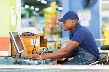 african male cashier working at till point