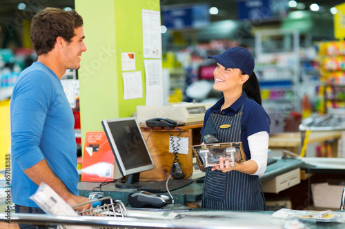 young man paying at till point in hardware store - 65788383
