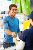 young man handing over credit card to a female cashier
