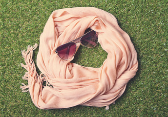 Summery pastel scarf and sunglasses on grass