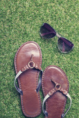 Summer sandals and sunglasses on grass