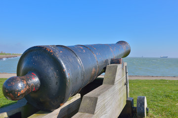 Old cannon on entrance to Slijk harbor