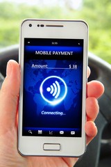 hand holding smartphone with mobile payment in the car