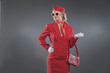 Retro fifties blonde stewardess wearing red suit with cap and su