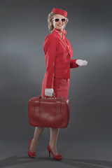 Retro blonde stewardess wearing red suit with cap and sunglasses