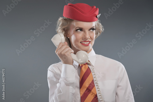 Smiling retro blonde stewardess wearing red cap with striped tie - 65794775