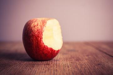 Half eaten apple on wooden table