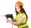 girl in a construction vest and a helmet with an electric drill.