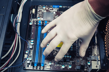 Gloved hand fixing computer