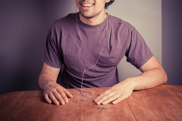 Young man sitting at a table with earphones