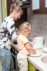 Mother and daughter kneading the dough together in kitchen
