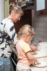 Mother and little daughter kneading dough together in kitchen