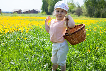 Small happy Caucasian girl standing on meadow with basket