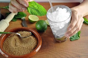hands preparing mojito cocktail