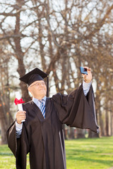 Mature man in graduation gown taking selfie