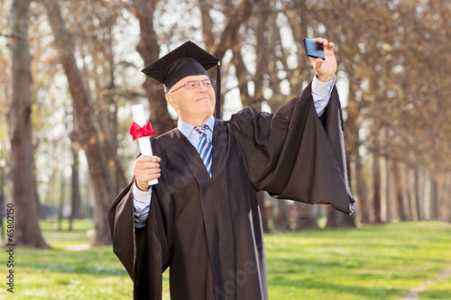 Mature graduate taking selfie in park