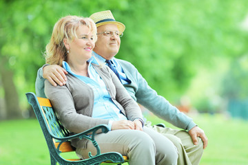 Mature couple sitting on a bench in park