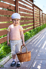 Pretty child with basket walking on house courtyard