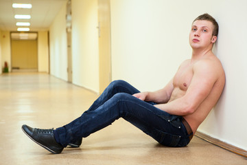 Depressive man with naked torso sitting in long corridor