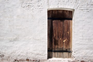 White old brick wall with weathered door