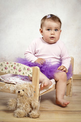 Little baby girl in tutu skirt sitting on the small bed