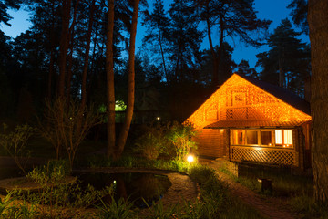 Cozy house by the pond in the conifer forest at night