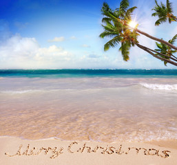 Merry Christmas written on tropical beach s.