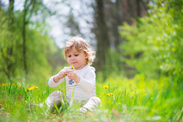 Little blonde girl in green grass