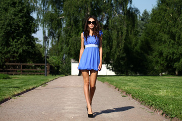 Happy young woman walking on the summer park