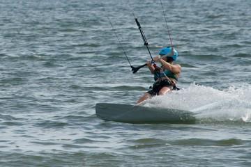Female kite surfer in helmet leaning over