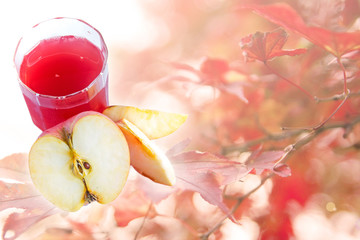 Apple juice and fresh apple on autumn background