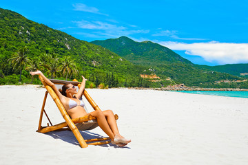 Attractive woman sunbathing alone during summer on the beach.