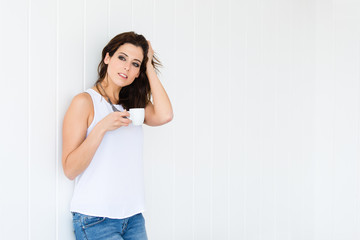Relaxed woman drinking coffee on white wall