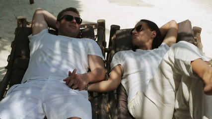 Couple lying on sunbeds and chatting, steadycam shot