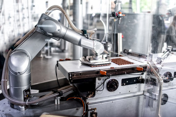automatic robotic hand moving and preparing bits of chocolate