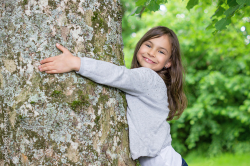 Little Girl holding big tree - 65814363