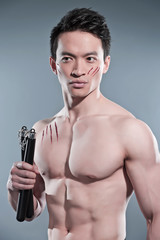 Muscled asian kung fu man with nunchucks. Blood scratches on his