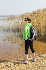 Woman stands at the reed-covered lake