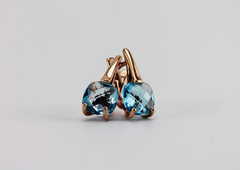 Jewelry. Gold earrings with blue Topaz. Isolated object on white