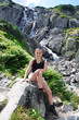 blond woman sitting on a rock in the mountains by the waterfall